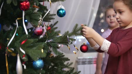 mensagens : Two little girls hang Christmas toys on the Christmas Tree, decorate the Christmas Tree for Santa Claus.