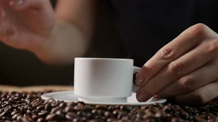 italian coffee : Coffee cup and coffee beans. A white cup of evaporating coffee on the table with roasted bean. Slow Motion coffee pour.