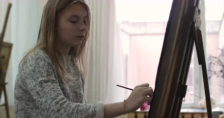 çizmek : Young Beautiful Female Artist is in an Art Studio, Sitting Behind an Easel and Painting on Canvas. Drawing Process: in the Art Studio of the Artists Hand Art Girl with a Brush Painting on Canvas.4K Stok Video