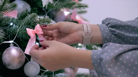 x mas : Young Hands of a woman spread a bow on the Christmas tree, decorate the festive Christmas tree with festive lights and Christmas balls.