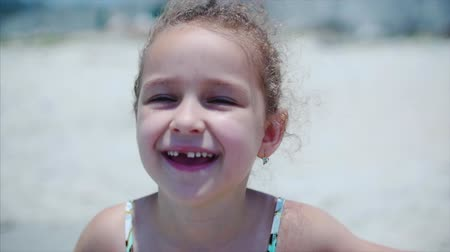 yapıştırma : Portrait of a charming little girl in a swimsuit. A child is standing on the beach smiling, looking at the camera. Stok Video