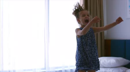ベッドルーム : Happy little Caucasian girl jumping on the bed. Slow motion.