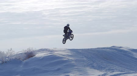 racers : Motorcycles, Children bikers rider on snowy motocross track. Rider on snow. Motocross rider on bike, motocross winter season race. Racer motorcycle rides on motocross snowy track in winter.