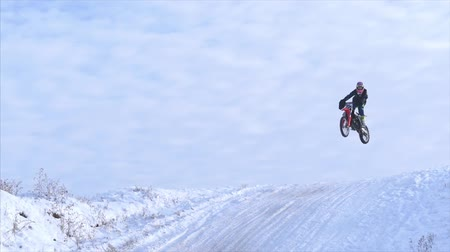 motorbike jump : Motorcycles, Children bikers rider on snowy motocross track. Rider on snow. Motocross rider on bike, motocross winter season race. Racer motorcycle rides on motocross snowy track in winter.
