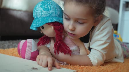 home school : Cute Little Girl with Curly Hair, in childrens pajamas, lying on the floor on a knitted carpet and herself reading a childrens book. Little girl reading a book hugging her soft baby doll.