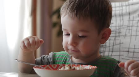 spoons : Cute little baby alone eats porridge with a spoon from a plate, the concept of healthy eating. Stock Footage