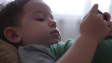 engrossed : Cute little boy playing on the phone, lying on his sofa, playing with the tablet computer.