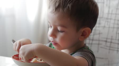 édesség : Cute little baby alone eats porridge with a spoon from a plate, the concept of healthy eating. Stock mozgókép