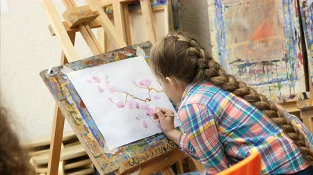 paleta : Little Girl artist draws at the easel. Drawing process: close-up of brush and canvas.
