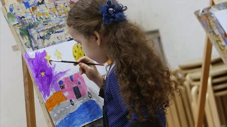 artistas : Young cute Female Artist is in an Art Studio, Sitting Behind an Easel and Painting on Canvas. Drawing Process: in the Art Studio of the Artists Hand Art Girl with a Brush Painting on Canvas. Vídeos