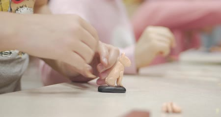 pré escolar : Cute Little Children Sitting at the Desk Sculpts a Different Figures From Made of Colored Modeling Plasticine in the Nursery. Development of the Art of Modeling in Children. Stock Footage