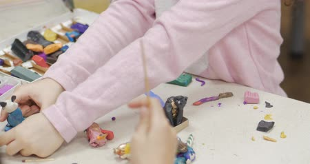 unknown : Cute Little Children Sitting at the Desk Sculpts a Different Figures From Made of Colored Modeling Plasticine in the Nursery. Development of the Art of Modeling in Children. Stock Footage