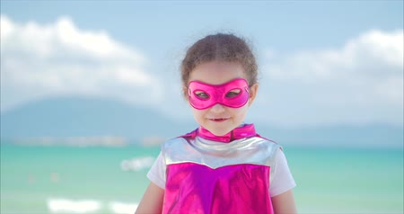 boyhood : Beautiful Little Girl in the Superhero Costume, Dressed in a Pink Cloak and the Mask of the Hero. Plays on the Background Sea and Blue Sky and Clouds, Sends a Fist Forward. Concept of a Happy Childhood.