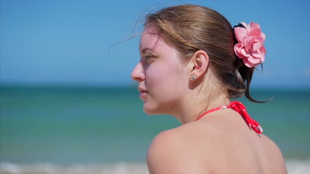 rendes : Portrait Close-Up of a Beautiful European Woman on the Beach, Looking into the Distance at the Sea, Relaxing at the Sea in the Summer. Stock Footage.