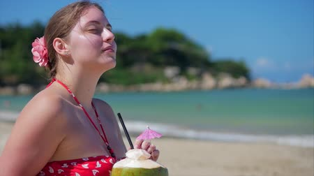 rendes : Close-Up Portrait of a European Beautiful Cute Brunette Young Woman or a Cheerful Girl, Drink a Coconut on Sun, in the Wind on a Tropical Beach. Concept Sea Waves Relaxing by the Sea in Summer.