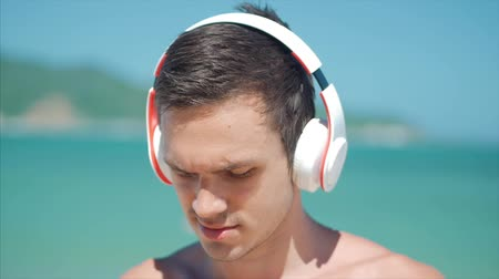 młodzież : Clouse Up Handsome Young Man Listening Music from his Smartphone in Wireless White Headphones, Dancing on Beach at Background Blue Sky.