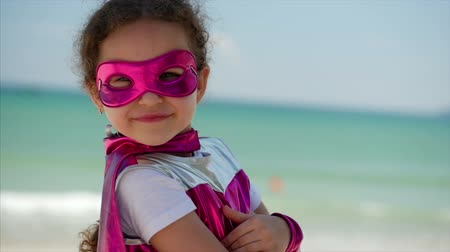 sen : Beautiful Little Girl in the Superhero Costume, Dressed in a Pink Cloak and the Mask of the Hero. Plays on the Background Sea and Blue Sky and Clouds, Sends a Fist Forward. Concept of a Happy Childhood.