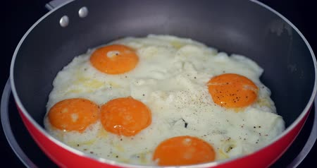 желток : The Chef Prepares Frying Eggs, Cook in Butter, Seasoned With Salt and Black Pepper and Green Onions in a Small Red Pan. Concept of Healthy Eating.