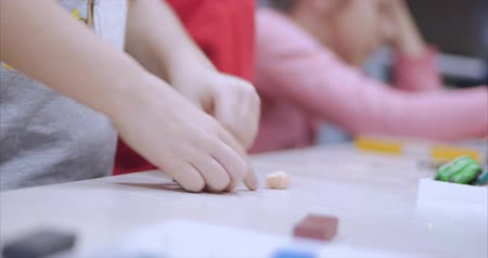 esculpir : Cute Little Children Sitting at the Desk Sculpts a Different Figures From Made of Colored Modeling Plasticine in the Nursery. Development of the Art of Modeling in Children. Vídeos