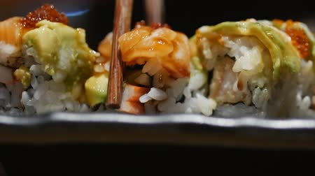 seafood recipe : Young Woman Hand with Sticks Takes Sushi. Concept Of Chinese Sticks Sushi Rolls on a Dark Plate. Stock Footage