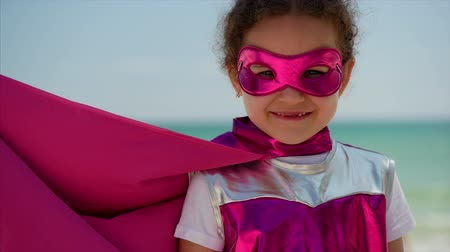 герой : Portrait Cute Little Girl in the Superhero Costume, Dressed in a Pink Cloak and the Mask of the Hero. Plays on the Background Sea and Blue Sky and Clouds. Concept of a Happy Childhood.
