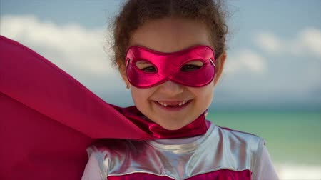 boyhood : Portrait Cute Little Girl in the Superhero Costume, Dressed in a Pink Cloak and the Mask of the Hero. Plays on the Background Sea and Blue Sky and Clouds. Concept of a Happy Childhood.