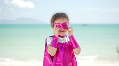 boyhood : Beautiful Llittle Girl in the Superhero Costume, Dressed in a Pink Cloak and the Mask of the Hero. Plays on the Background of the Sea and the Blue Sky and Clouds, Corrects the Pink Mask on His Face. Concept of a Happy Childhood.