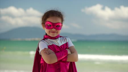 boyhood : Beautiful Little Girl in the Superhero Costume, Dressed in a Pink Cloak and the Mask of the Hero. Plays on the Background Sea and Blue Sky and Clouds. Concept of a Happy Childhood.