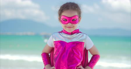 boyhood : Beautiful Little Girl in the Superhero Costume, Dressed in a Pink Cloak and the Mask of the Hero. Plays on the Background Sea and Blue Sky and Clouds, Sends a Fist Forward. Concept of a Happy Childhood. 4K