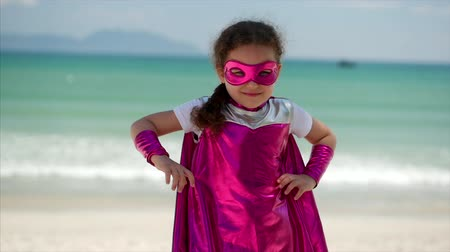 sen : Beautiful Little Girl in the Superhero Costume, Dressed in a Pink Cloak and the Mask of the Hero. Plays on the Background Sea and Blue Sky and Clouds, Puts Hands on Belt. Concept of a Happy Childhood.