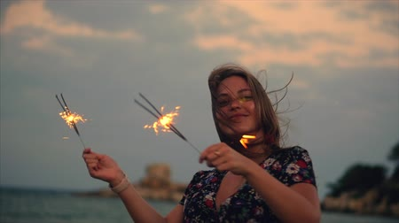 sparklers : Young Happy Smiling Woman, Dancing in With Sparkler at Sunset in Slow Motion, with Fireworks at Sunset on Beach. Stock Footage