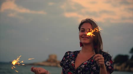 visszaszámlálás : Young Happy Smiling Woman, Dancing in With Sparkler at Sunset in Slow Motion, with Fireworks at Sunset on Beach. Stock mozgókép