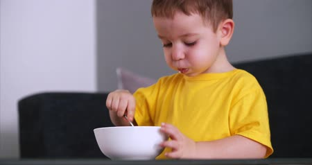 kendi : Small Cute Child is Sitting at a Table and eat his own oatmeal, the baby eats willingly. Concept Happy Childhood. Stok Video
