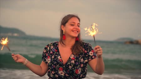 photograph : Young Happy Smiling Woman, Dancing in With Sparkler at Sunset in Slow Motion, with Fireworks at Sunset on Beach. Stock Footage