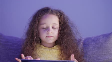 ebook : Night Shot Portrait of a Caucasian Cute Child, Little Baby Girl Close Up of a Childs Face Viewing a Tablet PC With a Reflection of and Pictures in His Eyes.
