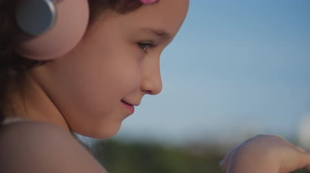curly haired : Portrait of a Cute Child with curly hair, Caucasian Little Girl in a Pink Dress With a Pink Flower on Her Head in Her Hair,Baby in Pink Headphones Listening music,Looking at the Camera,Smiling Sweetly Stock Footage