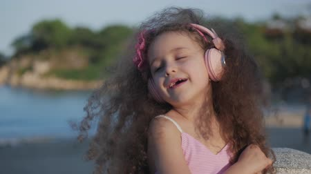 nyomasztó : Portrait of a Cute Child with curly hair, Beatiful Caucasian Little Girl Summer in a Pink Dress With a Pink Flower on Her Head in Her Hair,Baby in Pink Headphones Listen to Music, Smiling Sweetly.