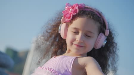 curly haired : Portrait of a Cute Child with curly hair, Beatiful Caucasian Little Girl Summer in a Pink Dress With a Pink Flower on Her Head in Her Hair,Baby in Pink Headphones Listen to Music, Smiling Sweetly.