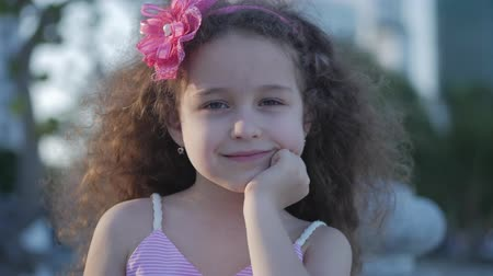 curly haired : Portrait Cute little Child Caucasian Female, Kid Outdoors in a Pink Dress with a Pink Flower on Her Head, Beautiful Little Girl Summer in Park and Smiling Sweetly. Concept Happy childhood. Stock Footage