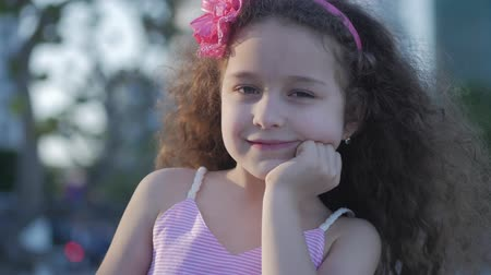 curly haired : Portrait Cute little Child Caucasian Female, Kid Outdoors in a Pink Dress with a Pink Flower on Her Head, Looking in the Camera. Concept Happy childhood. Stock Footage