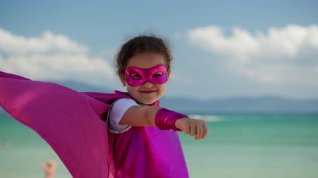 plášť : Beautiful Little Girl in the Superhero Costume, Dressed in a Pink Cloak and the Mask of the Hero. Plays on the Background Sea and Blue Sky and Clouds, Sends a Fist Forward. Concept of a Happy Childhood.
