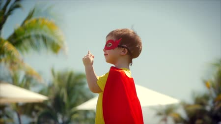érdemes : Beautiful Little Boy in a Superhero Costume, Dressed in a Cloak and Mask of a Hero, is Worth Considering Hands. Concept of a Happy Childhood.