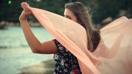 красные волосы : Young Cute Brown-Haired Woman With Green Eyes with Flowing Hair in a Summer Dress with a Picture of Red and White Flowers Spinning Around with Scarf at a Beach at Set Sun. Soft focus. Стоковые видеозаписи
