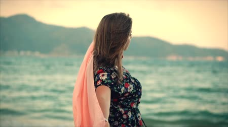stal : Close up Portrait a Beautiful Brown-Haired Woman With Green Eyes with Flowing Hair in a Summer Dress with a Picture of Red and White Flowers Spinning Around with Scarf at a Beach at Set Sun.Soft focus Stockvideo