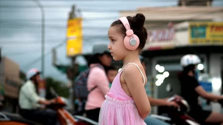 curly haired : Portrait of a Cute Child Standing By the Road, a Wonderful Little Cute Girl in a Pink Dress and Pink Headphones Looking Away, Against the Background of Passing Cars and Motorcycles.