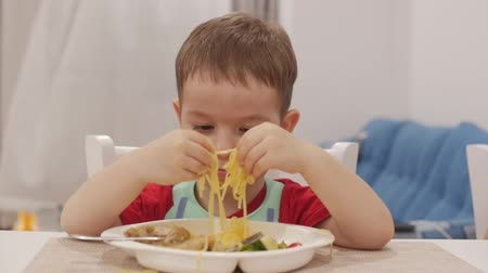 ártatlanság : Small Child is Sitting at a Table in a Bib and Eat His Own Spaghetti, the Cute Baby Eats Willingly. Cute Little Baby Eating Her Dinner. 4K