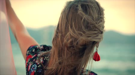 rudé moře : Close up Portrait a Wonderful Brown-Haired Woman With Green Eyes with Flowing Hair in a Summer Dress with a Picture of Red and White Flowers Spinning Around with Scarf at a Beach at Set Sun.Soft focus Dostupné videozáznamy