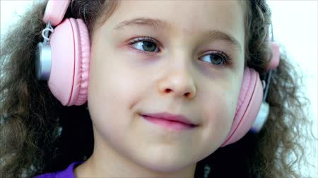 curly haired : Portrait of a Cute Child with curly hair, Caucasian Little Girl in a Purple t-shirt With a Pink Headphones Listening music,Looking at the Camera,Smiling Sweetly.