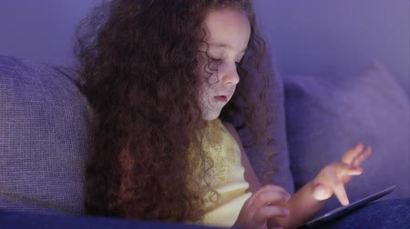 use computer : Cute Child Entertaining With Tablet. Little Girl Spending Leisure Time Playing Mobile Game in the and Crushes the Bright Screen With Her Hand. Concept of:Happy Childfood, Technology, Childen Play Games.