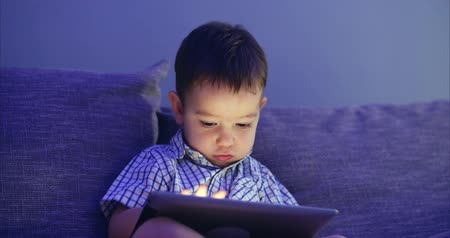 use laptop : Cute Child Entertaining With Tablet. Little Boy Spending Leisure Time Playing Mobile Game in the and Crushes the Bright Screen With Her Hand. Concept of:Happy Childfood, Technology, Childen Play Games.